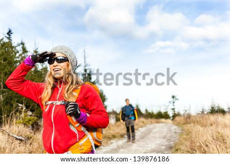 Man and woman hikers trekking on dirt road in mountains. Young couple on cold holidays in forest.
