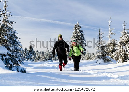Man and woman hikers walking in winter mountains. Young couple happy walking no white snow in mountain forest, Poland - stock photo