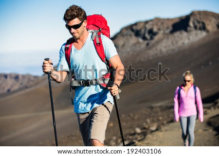 Man and woman hiking on beautiful mountain trail. Trekking and backpacking in the mountains. Healthy lifestyle outdoor adventure concept. - stock photo