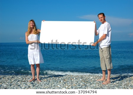 Man and woman holding blank billboard