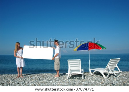 Man and woman holding blank placard on a beach