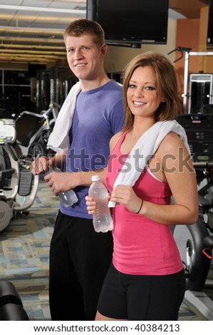 Man and woman holding bottled water at the gym