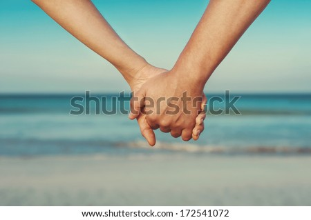 Man and woman holding by hands against the sea - stock photo