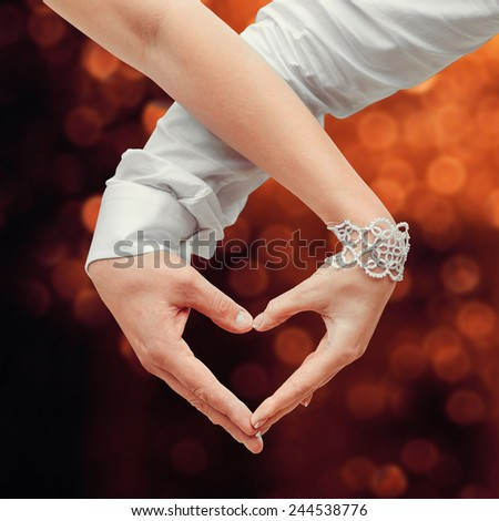 Man and woman holding by hands and making love heart - stock photo