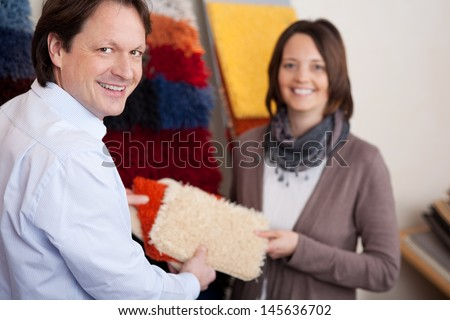 Man and woman holding choosing a new carpet - stock photo