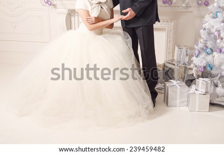Man and woman holding each other's hands. Bride and groom on the background of a New Year's interior room. Hands close up. Christmas Festive concept for the original wedding day. Happy New Year. - stock photo