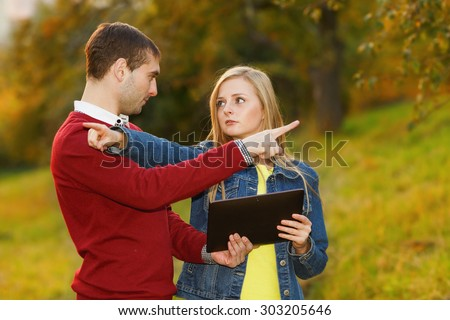 Man and woman holding electronic tablet in hands, argue where to go. Point the finger in different directions. Young students. September, October, golden autumn. Traveler, tourist, navigator, lose. - stock photo
