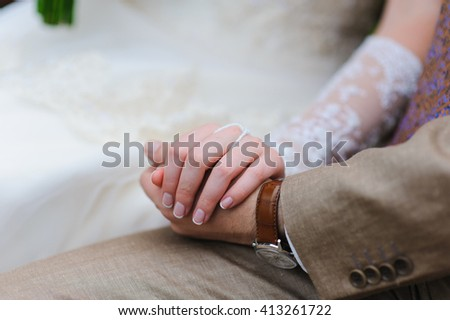 Man and woman holding hands. A pair of lovers sit and hold hands. The groom in a suit, the bride in a wedding dress. - stock photo