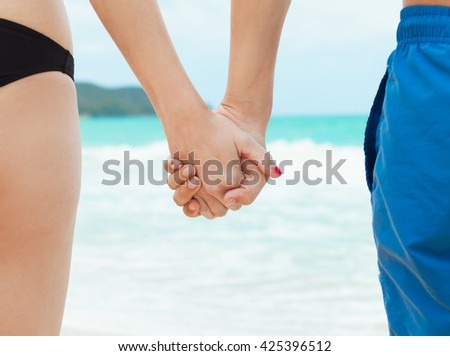 Man and woman holding hands on the beach. - stock photo