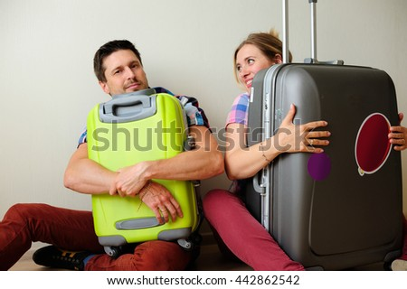 man and woman hug suitcase.