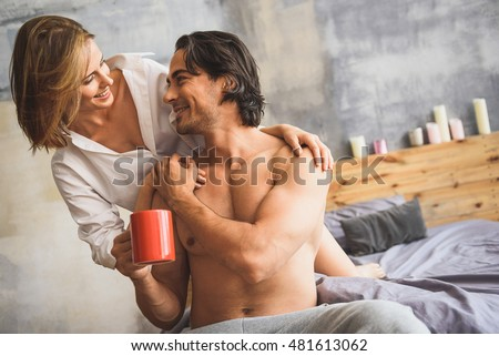man and woman hugging in a bed