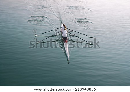 Man and woman in a boat, rowing on the tranquil lake - stock photo