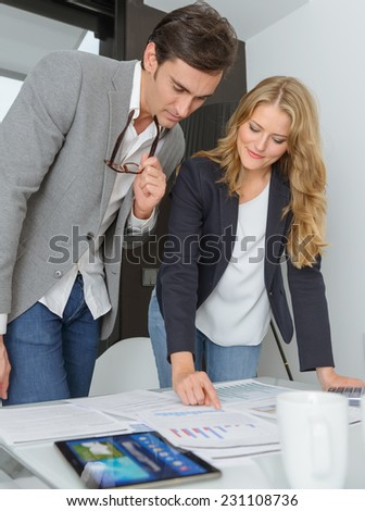 Man and woman in casual business clothes discussing business plan - stock photo