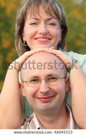 man and woman in early fall park. woman's hands on man's head - stock photo