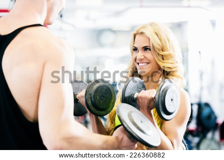 Man and woman in fitness gym lifting dumbbells looking at each other  - stock photo