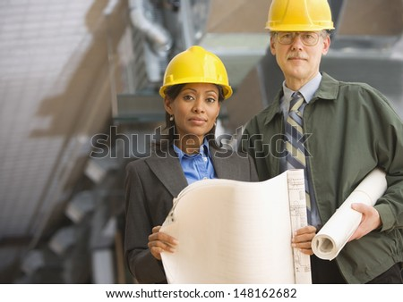 Man and woman in hard hats holding blueprints