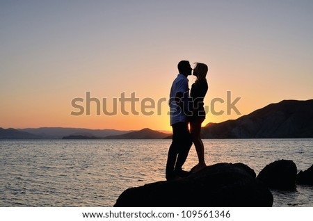 Man and woman in his arms against the sea and sunset - stock photo