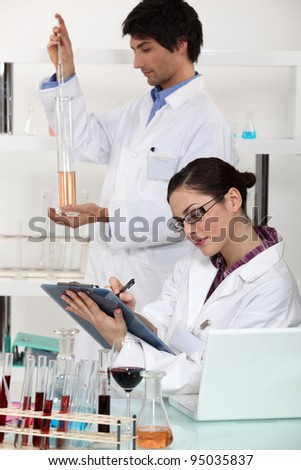 Man and woman in laboratory - stock photo