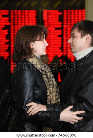 Man and woman in leather jacket standing in profile and embracing look to each other in eye on background of flight timetable - stock photo