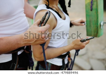 man and woman in safety equipment are holding harnesses carabiners closeup. climbing, sports ekstrim