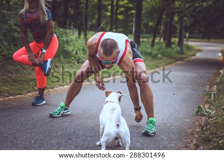 Man and woman in sportswear doing exercises and their dog on the forest road.  - stock photo