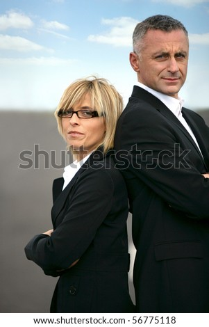 Man and woman in suit standing back to back