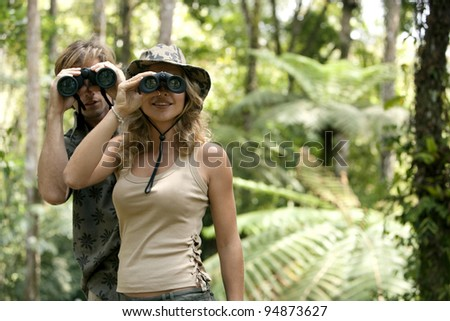 Man and woman in the forest looking at the camera through binoculars. - stock photo
