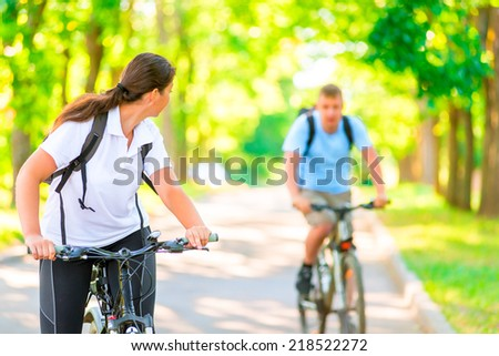 man and woman in the park on bicycles in the morning - stock photo