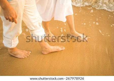 Man and woman in white dress walking on the beach with copy space - stock photo