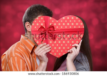 Man and woman kissing in a heart-shaped box - stock photo
