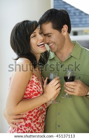 Man and woman laugh while standing with glasses of wine. Vertical shot. - stock photo