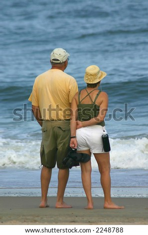 Man and woman looking out over the ocean - stock photo