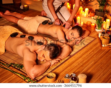 Man and woman luxuriate in bamboo spa. - stock photo