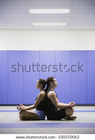 Man and woman meditating back to back - stock photo