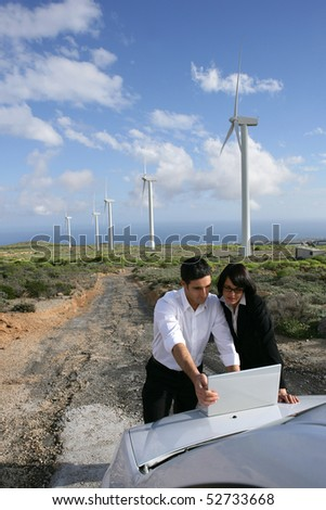 Man and woman next to wind turbines with a laptop computer - stock photo