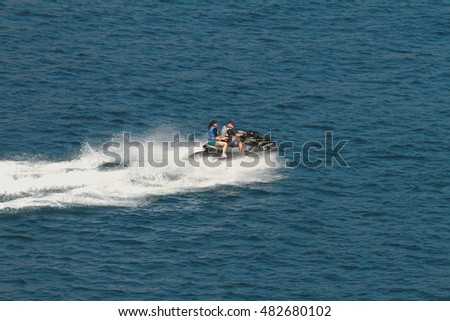 Man and woman on hydrocycle in sea