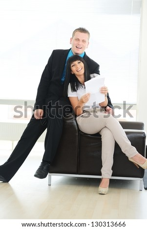 Man and woman on leather sofa smiling and having good time - stock photo