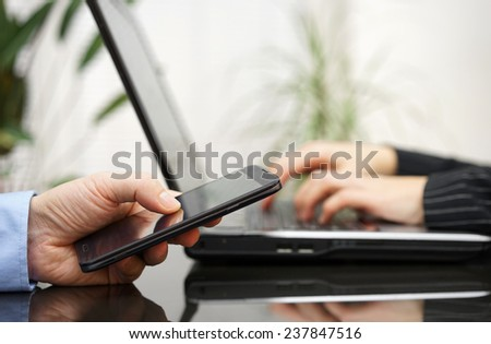 Man and woman on meeting  are using laptop computer and mobile smart phone