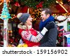 "Man and woman or  a couple  or friends during advent season or holiday in front of a carousel or ""marry-go-round"" on the Christmas or Xmas market - stock photo"