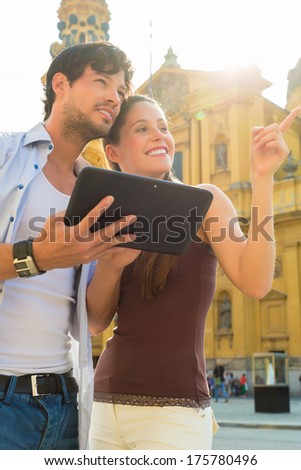 Man and woman or young couple making trip as tourists in Munich at the Odeon Church with city map on the tablet computer for navigation - stock photo