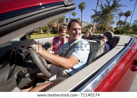 Man and woman parents and two children having fun driving in a red convertible car in sunshine - stock photo
