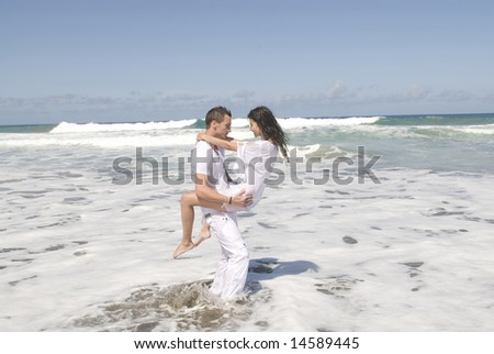 man and woman playing in the seaside with copy space