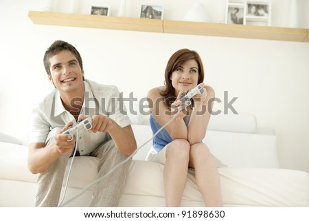 Man and woman playing video games at home. - stock photo