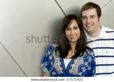 Man and woman posing together against concrete wall - stock photo