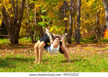 Man and woman practice Yoga dhanurasana under urdhva dhanurasana pose in forest - stock photo