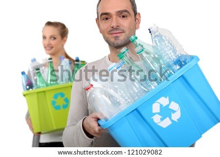 Man and woman recycling plastic bottles