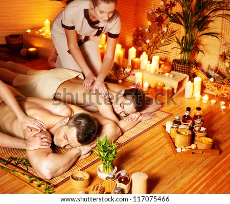 Man and woman relaxing in bamboo spa.