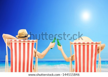 Man and woman relaxing on a beach and cheering with beer bottles - stock photo