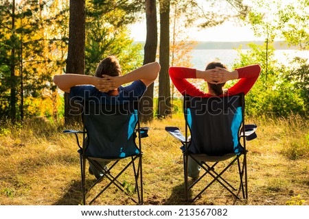 man and woman resting on the lake - stock photo