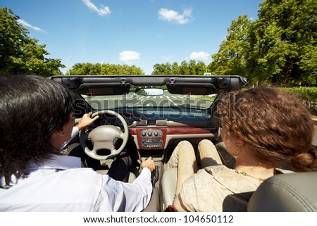 Man and woman ride in a convertible along asphalt road, back view - stock photo
